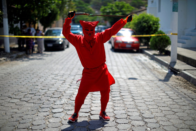 A man dressed as a demon poses for a picture as he participates in a ceremony known as Los Talciguines, as part of religious activities to mark the start of the Holy Week in Texistepeque, El Salvador, March 26, 2018. (Photo by Jose Cabezas/Reuters)