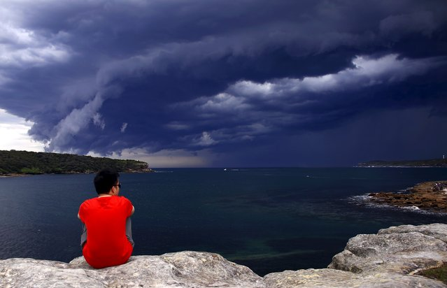 A Chinese tourist watches storm clouds moving along the coast towards the city of Sydney, Australia, November 6, 2015. (Photo by David Gray/Reuters)