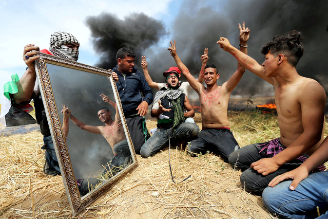 Palestinian activists are seen reflected in a mirror as they gather at the Israel-Gaza border, in the southern Gaza Strip April 2, 2018. Picture taken April 2, 2018. (Photo by Ibraheem Abu Mustafa/Reuters)