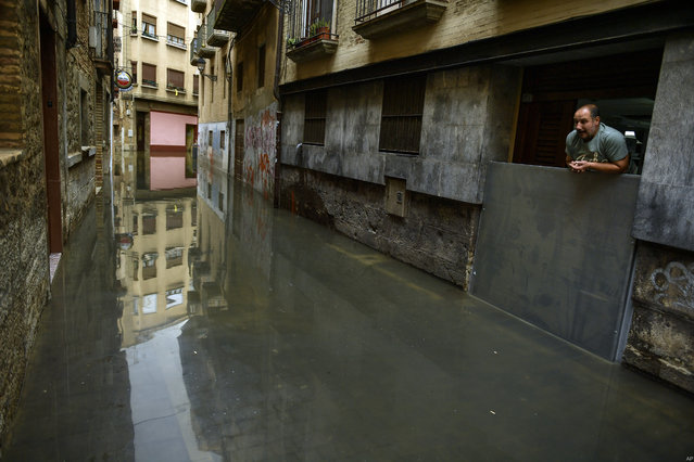 A man looks down from the door of a house affected by water from the Ebro River, in Tudela, northern Spain, Friday, April 13, 2018. Heavy rain has lead to flooding in northern Spain over the past few days, especially in Navarra provinces and Aragon. (Photo by Alvaro Barrientos/AP Photo)