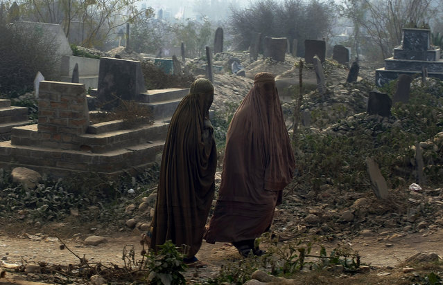 Pakistani women leave the Rahman Baba graveyard after offering prayers at the graves of victims in Tuesday's school massacre in Peshawar, Pakistan, Saturday, December 20, 2014. Taj Muhammad, one of the gravediggers at Peshawar's largest graveyard has a rule. He said he never cries when he buries the dead. He's a professional, he said. But as the dead bodies, mostly children, started coming in from a school massacre this week that killed 148 people, he began to weep. (Photo by Mohammad Sajjad/AP Photo)