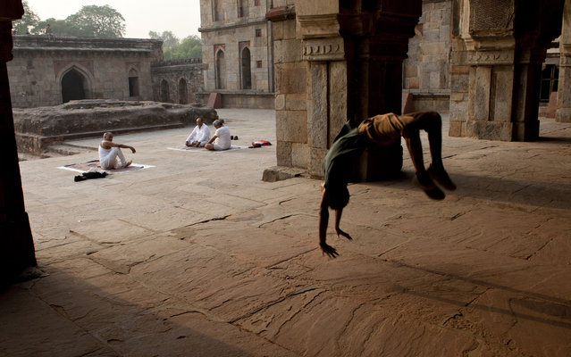 A young dancer practicing pirouettes while participants performed yoga exercise at the bottom in front of the Mosque of Three Domes in Lodi Gardens in New Delhi, India, on May 7, 2013. (Photo by Tengku Bahar/AFP Photo)