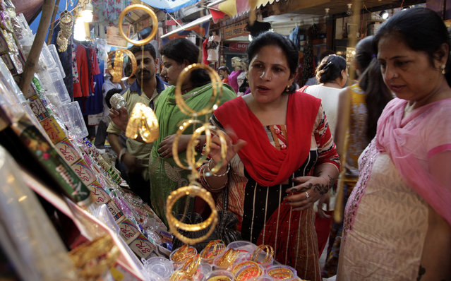 Indian women shop for bangles on the eve of the Hindu festival of Karva Chauth in Jammu, India, Tuesday, October 18, 2016. Married Hindu women decorate their hands with henna, wear colorful bangles and observe a fast to pray for the longevity and well being of their husbands during this festival. (Photo by Channi Anand/AP Photo)