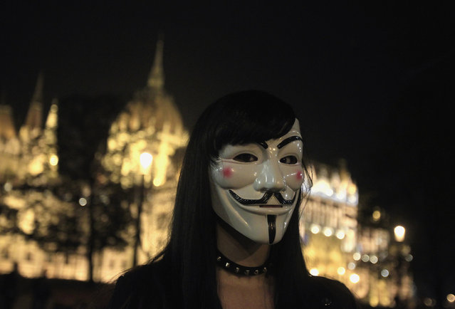"""Hungary: A protester wearing a Guy Fawkes mask stands in front of the Hungarian Parliament during a demonstration by supporters of the Anonymous movement as part of the global """"Million Mask March"""" protests in Budapest, November 5, 2014. (Photo by Bernadett Szabo/Reuters)"""