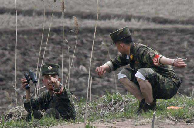 A North Korean soldier gestures toward a Chinese tourist boat after monitoring with a pair of binoculars on the bank of Hwanggumpyong island located in the middle of the Yalu River, near the North Korean town of Sinuiju and the Chinese border city of Dandong, April 30, 2012. (Photo by Jacky Chen/Reuters)