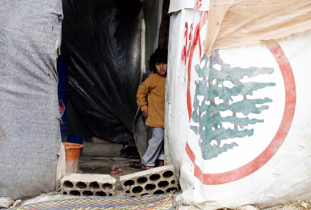 A Syrian refugee girl looks out from a tent at a makeshift settlement in Bar Elias in the Bekaa valley January 5, 2015. (Photo by Mohamed Azakir/Reuters)