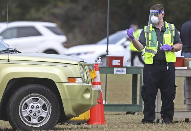 A health worker directs a vehicle before administering a COVID-19 vaccine to one of about 300 people to get vaccinated, Wednesday, December 30, 2020, at the Manatee County Public Safety Center in Bradenton, Fla. (Photo by Scott Keeler/Tampa Bay Times via AP Photo)