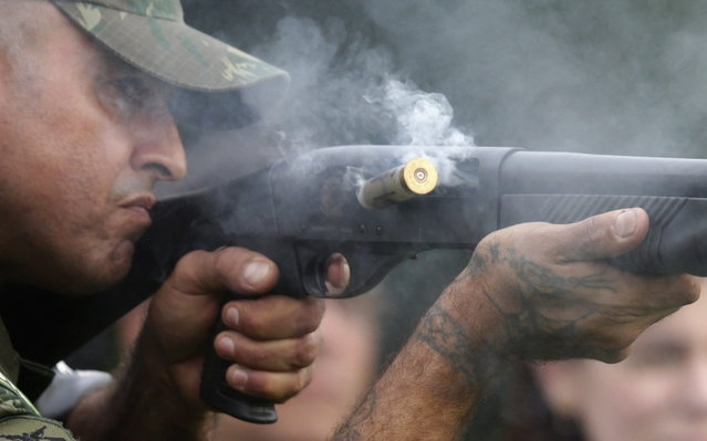 A Brazilian Navy member ejects spent cartridges while shooting rubber bullets during an exhibition of their operational capacity to combat terrorist attacks and riots ahead of the FIFA Confederations Cup and World Youth Day in Rio de Janeiro on May 27, 2013. (Photo by Ricardo Moraes/Reuters)