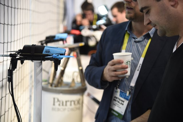 Attendees look at the Parrot BeBop Drone Quadcopter with Skycontroller, January 6, 2015 at the Consumer Electronics Show in Las Vegas, Nevada. (Photo by Robyn Beck/AFP Photo)
