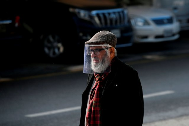 A man wearing a face shield as a preventive measure against the Covid-19 coronavirus walks along a street in Islamabad on December 9, 2020. (Photo by Aamir Qureshi/AFP Photo)