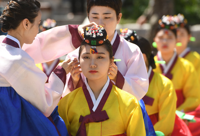 A young South Korean woman wears a traditional Korean flower cap during a traditional Coming-of-Age Day ceremony to mark adulthood at Namsan hanok village in Seoul on May 21, 2018. The ceremony marks the age of 19, at which a person is legally able to make life choices from voting, to drinking alcohol. (Photo by Jung Yeon-Je/AFP Photo)