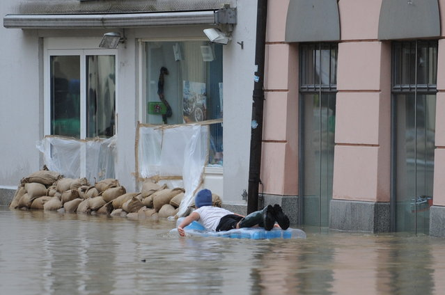 A man on a inflatable mattress paddles through a overflooded street in Passau, southern Germany, on June 3, 2013. Parts of the eastern and southern Germany were flooded due to heavy and ongoing rainfalls. (Photo by Andreas Gebert/AFP Photo)