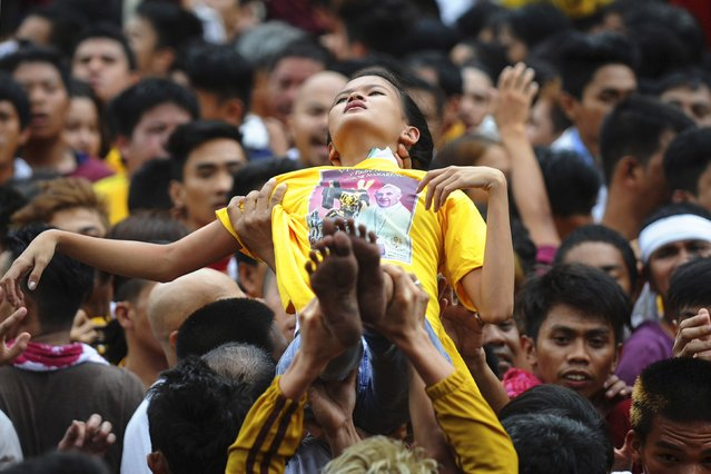 Devotees of the Black Nazarene lifts-up a woman who fainted during an annual procession in Manila January 9, 2015. (Photo by Ezra Acayan/Reuters)