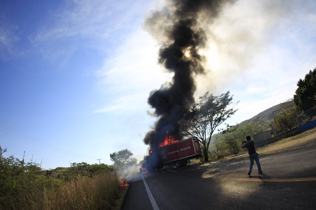 A man takes pictures of a truck burned by activists after a demonstration at the military zone of the 27th infantry battalion, on the outskirts of Iguala, Guerrero, January 12, 2015. (Photo by Jorge Dan Lopez/Reuters)