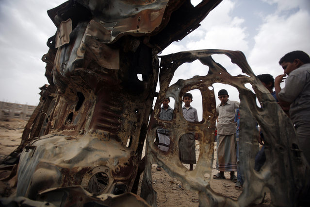 Boys gather near the wreckage of car destroyed last year by a U.S. drone air strike targeting suspected al Qaeda militants in Azan of the southeastern Yemeni province of Shabwa February 3, 2013. (Photo by Khaled Abdullah/Reuters)