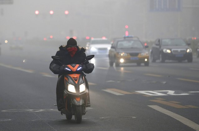 A man covers his mouth with a scarf along Chang'an Avenue as smog covers China's capital Beijing on an extremely polluted day, December 1, 2015. (Photo by Jason Lee/Reuters)