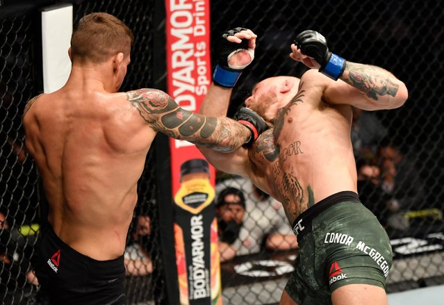 (L-R) Dustin Poirier punches Conor McGregor of Ireland in a lightweight fight during the UFC 257 event inside Etihad Arena on UFC Fight Island on January 23, 2021 in Abu Dhabi, United Arab Emirates. (Photo by Jeff Bottari/Zuffa LLC)