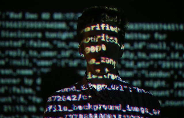 A staff member stands in a projection of live data feeds from (L-R) Twitter, Instagram and Transport for London at the Big Bang Data exhibition at Somerset House on December 2, 2015 in London, England. The show highlights the data explosion that's radically transforming our lives. (Photo by Peter Macdiarmid/Getty Images for Somerset House)