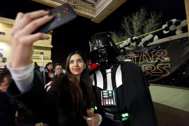 A woman takes a selfie with a person dressed as the character Darth Vader during a Star Wars fan convention in Ciudad Juarez, Mexico December 5, 2015. (Photo by Jose Luis Gonzalez/Reuters)