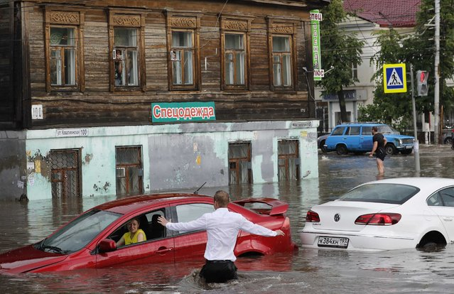 A woman is rescued from her flooded car at the street in Nizhny Novgorod, Russia on June 19, 2018. (Photo by Murad Sezer/Reuters)