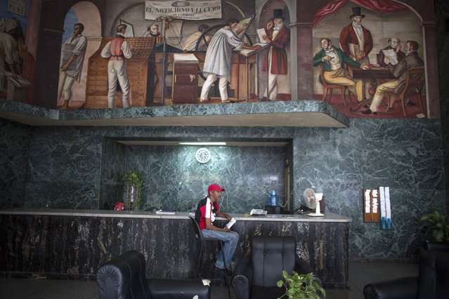 Chef Enrique Larrinaga, 59, sits after the end of his shift at the reception area of an editorial where he works in downtown Havana, January 15, 2015. (Photo by Alexandre Meneghini/Reuters)