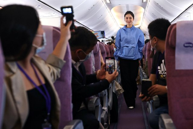 A flight attendant wearing an Xpore top designed for safe traveling, walks the catwalk during a sightseeing flight, amid the spread of the coronavirus disease (COVID-19), in Taipei, Taiwan on November 19, 2020. (Photo by Ann Wang/Reuters)