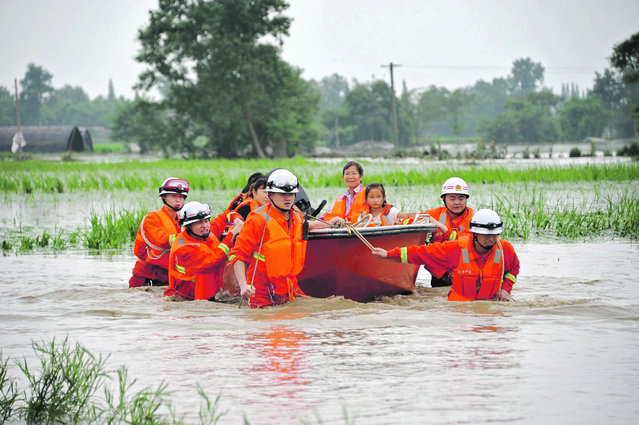 Rescue workers pull a boat carrying villagers away from a flooded area in Guanghan, Sichuan province, July 11, 2013. (Photo by Reuters/China Daily)