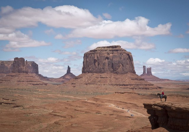 A Navajo man on a horse poses for tourists in front of the Merrick Butte in Monument Valley Navajo Tribal park, Utah, on May 12, 2014. Monument Valley has been featured in many Westerns since the 1930s, including director John Ford's best-known movies and has become the epitome of the American West. (Photo by Mladen Antonov/AFP Photo)