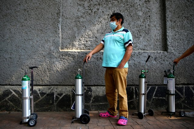 A man queue to fill oxygen in a tank for a relative due to an increase in coronavirus disease (COVID-19) infection rates in Mexico, outside a medical supply store in Mexico City, December 21, 2020. (Photo by Edgard Garrido/Reuters)