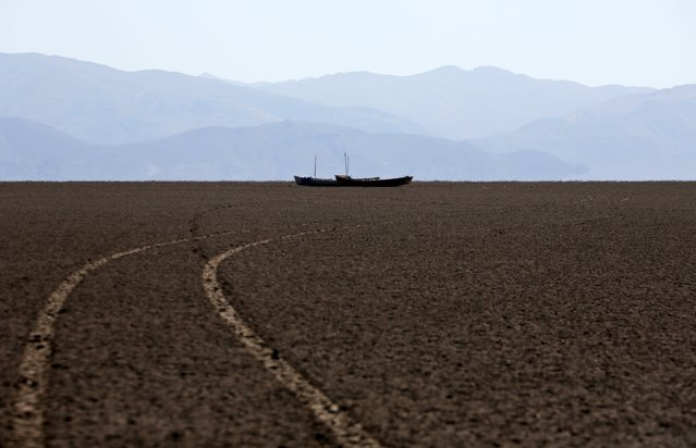 Boats of fishermen are seen on the dried Poopo lakebed in the Oruro Department, south of La Paz, Bolivia, December 17, 2015. (Photo by David Mercado/Reuters)
