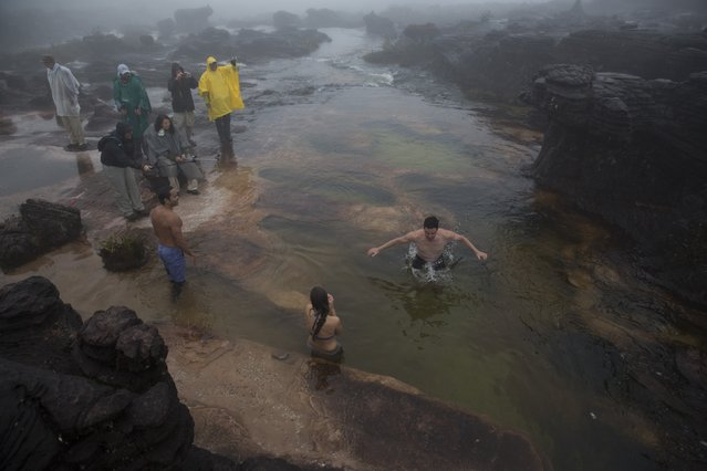 Tourists bathe on a river at the top of Roraima Mount, near Venezuela's border with Brazil January 15, 2015. (Photo by Carlos Garcia Rawlins/Reuters)