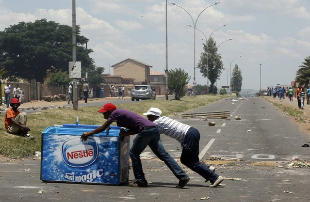 Locals push a freezer after looting it from a shop, believed to be owned by a foreigner, during service delivery protests in Mohlakeng, west of Johannesburg, February 4, 2015. Local media reported that violence broke out on Wednesday morning when locals barricaded roads and burnt tyres during a service delivery protest. (Photo by Siphiwe Sibeko/Reuters)
