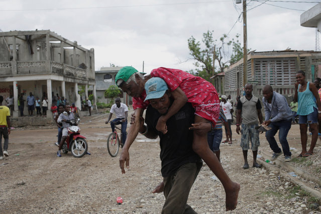 A man carries a disabled woman to go to vote in a street of Port-a-Piment, Haiti, November 20, 2016. (Photo by Andres Martinez Casares/Reuters)