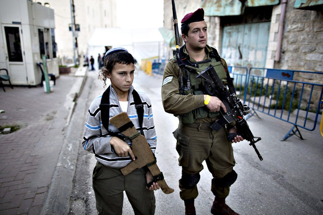 A young settler holding a wooden rifle stands next to an Israeli soldier as he  secures a street during the visit of Israeli President Reuven Rivlin at the Cave of the Patriarchs in the Old City of West Bank city Hebron, 02 February 2015. Rivlin came to Hebron to inaugurate a newly developed Hebron Heritage Museum. (Photo by Abir Sultan/EPA)
