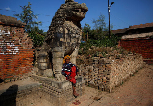 A woman sits below a statue of a deity in Bhaktapur, Nepal November 23, 2016. (Photo by Navesh Chitrakar/Reuters)
