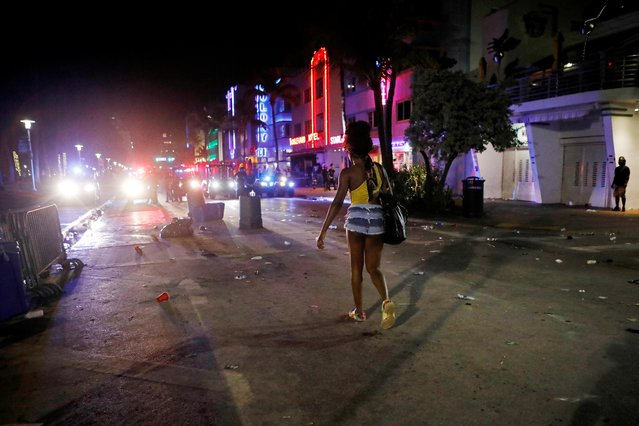 A woman walks in front of police officers enforcing an 8pm curfew imposed by local authorities on spring break festivities, amid the coronavirus disease (COVID-19) pandemic, in Miami Beach, Florida, U.S., March 20, 2021. (Photo by Marco Bello/Reuters)