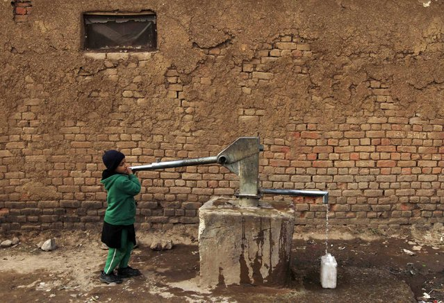 A girl collects drinking water for her family at a slum on the outskirts of Islamabad February 6, 2015. (Photo by Faisal Mahmood/Reuters)