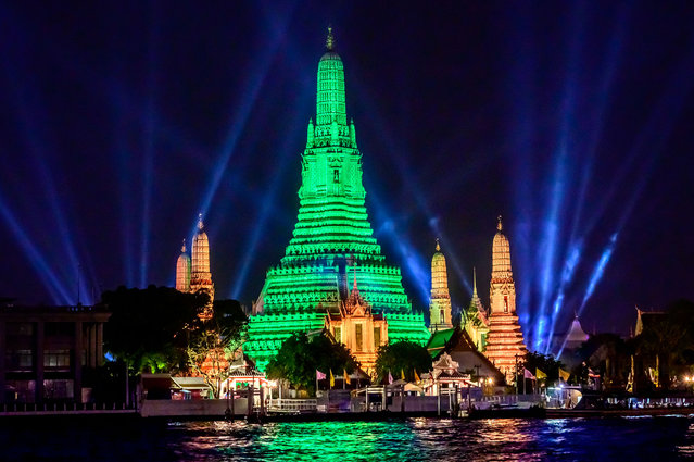 The stupa of the Buddhist temple Wat Arun (Temple of Dawn) is illuminated in green to mark St. Patrick's Day in Bangkok on March 17, 2021. (Photo by Mladen Antonov/AFP Photo)