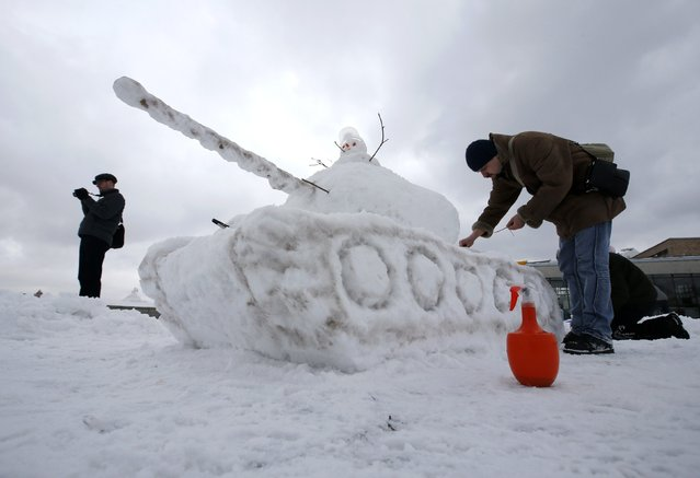 A man works on a snow sculpture of a tank during an amateur snowman parade and contest in Moscow February 7, 2015. (Photo by Sergei Karpukhin/Reuters)