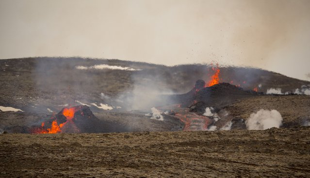 Steam and lava spurt from a new fissure on a volcano on the Reykjanes Peninsula in southwestern Iceland, Monday, April 5, 2021. The new fissure has opened up at the Icelandic volcano that began erupting last month, prompting the evacuation of hundreds of hikers who had come to see the spectacle. Officials say the new fissure is about 500 meters (550 yards) long and about one kilometer (around a half-mile) from the original eruption site in the Geldinga Valley. (Photo by Marco Di Marco/AP Photo)
