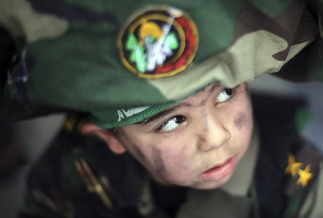 A Palestinian boy wearing the headband of Hamas' armed wing attends Friday prayers during a protest against the decision of an Egyptian court to list Hamas' armed wing as a terrorist organization, outside the Egyptain embassy in Gaza City February 6, 2015. (Photo by Mohammed Salem/Reuters)