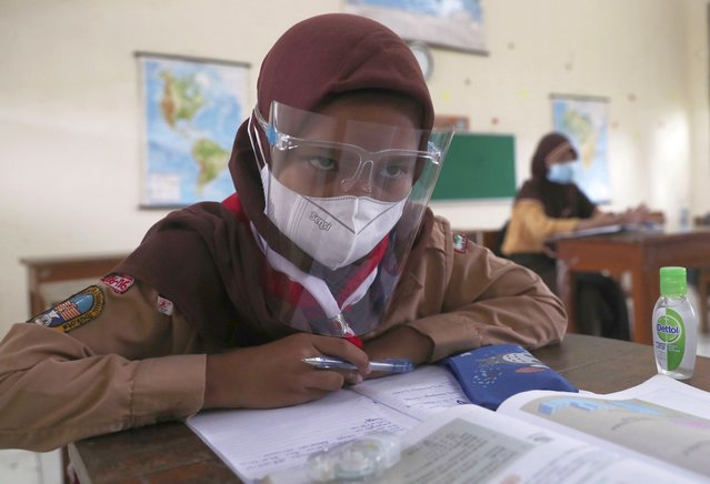 A student wearing a face shield sits spaced apart during a trial run of a class with COVID-19 protocols at an elementary school in Jakarta, Indonesia, Wednesday, April 7, 2021. (Photo by Tatan Syuflana/AP Photo)