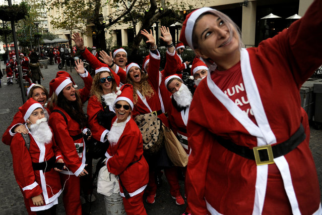 People dressed in Santa costumes take a selfie as they take part in the Santa Run Athens, in Athens, Greece,  December 4, 2016. (Photo by Michalis Karagiannis/Reuters)