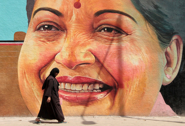 A woman walks past a portrait of J. Jayalalithaa, Chief Minister of the southern state of Tamil Nadu, in Chennai, India, March 13, 2012. (Photo by Reuters/Babu)