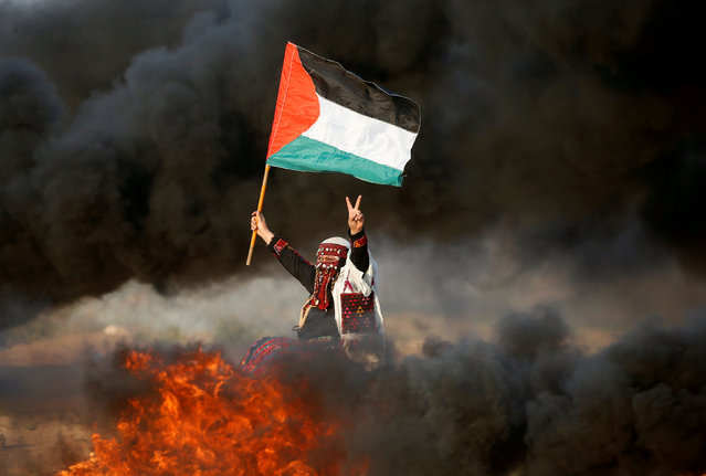 A woman waves a Palestinian flag during a protest calling for lifting the Israeli blockade on Gaza and demanding the right to return to their homeland, at the Israel-Gaza border fence east of Gaza City September 28, 2018. (Photo by Mohammed Salem/Reuters)