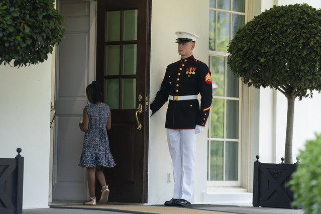 A Marine holds the door as Gianna Floyd, the daughter of George Floyd, walks into the White House, Tuesday, May 25, 2021, in Washington. (Photo by Evan Vucci/AP Photo)
