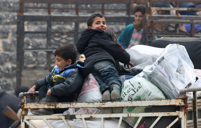 Boys react as they sit on belongings and wait to be evacuated from a rebel-held sector of eastern Aleppo, Syria December 16, 2016. (Photo by Abdalrhman Ismail/Reuters)