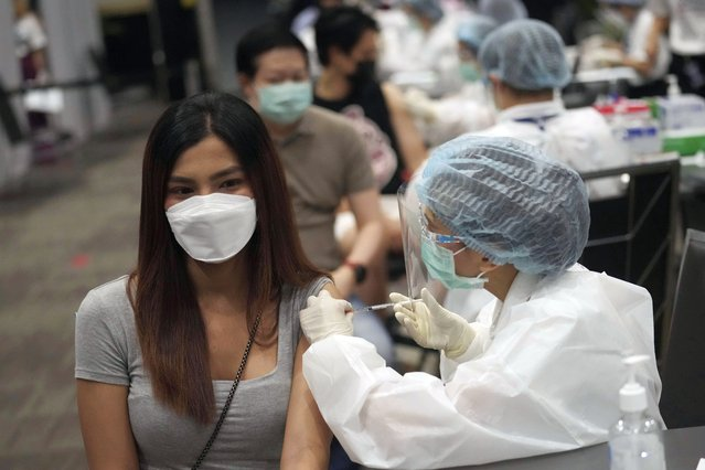 A health worker administers a dose of the AstraZeneca COVID-19 vaccine to a woman at Paragon shopping mall in Bangkok, Thailand, Monday, June 7, 2021. Health authorities in Thailand on Monday began their much-anticipated mass rollout of locally produced AstraZeneca vaccine, but it appeared that supplies were falling short of demand from patients who had scheduled vaccinations for this week. (Photo by Sakchai Lalit/AP Photo)