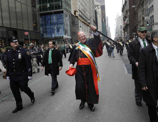 The Grand Marshall of the St. Patrick's Day Parade, Archbishop Timothy Dolan, walks past protesters during the St. Patrick's Day Parade in New York, Tuesday, March 17, 2015. A group of people along the parade route were protesting the exclusion of LGBT groups from the parade. (Photo by Seth Wenig/AP Photo)