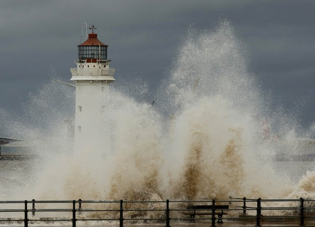 Waves break over the promenade in front of Perch Rock lighthouse off New Brighton beach, near Wallasey in Britain January 26, 2016. (Photo by Phil Noble/Reuters)